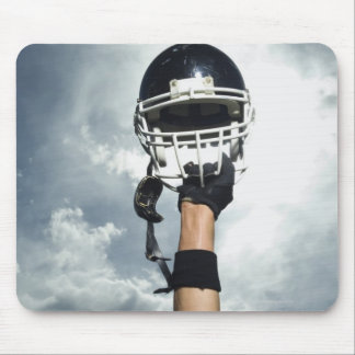 Football player holding helmet in air mouse pads