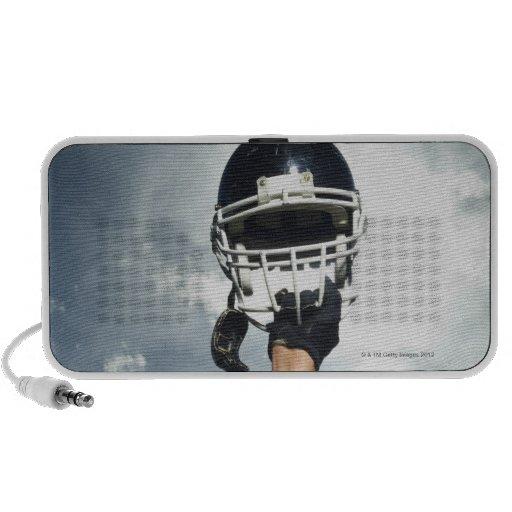 Football player holding helmet in air travel speaker