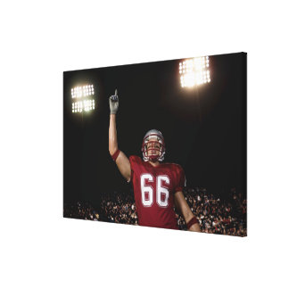 Football player holding up index finger stretched canvas print