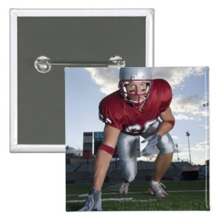 Football player in game stance pinback buttons