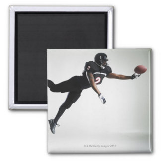 Football player leaping in mid air to catch ball 2 inch square magnet