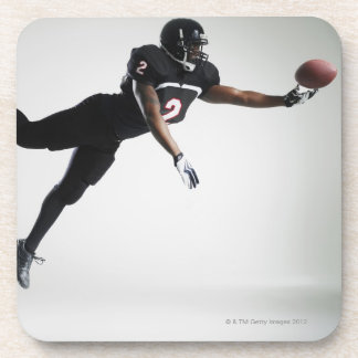 Football player leaping in mid air to catch ball beverage coaster