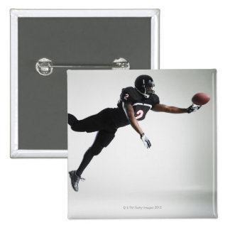 Football player leaping in mid air to catch ball button
