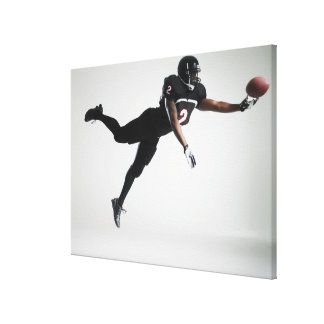 Football player leaping in mid air to catch ball canvas print