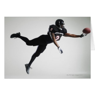 Football player leaping in mid air to catch ball greeting card