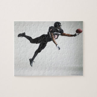 Football player leaping in mid air to catch ball jigsaw puzzle
