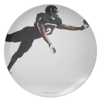 Football player leaping in mid air to catch ball dinner plates