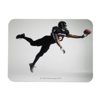 Football player leaping in mid air to catch ball rectangular photo magnet