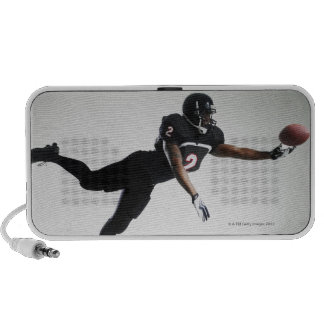 Football player leaping in mid air to catch ball laptop speaker