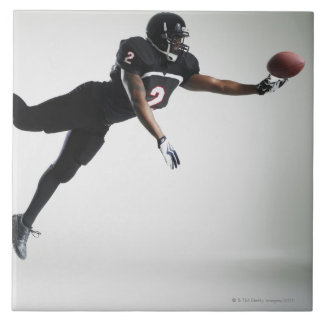 Football player leaping in mid air to catch ball tile