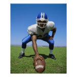 football player playing on a football field poster