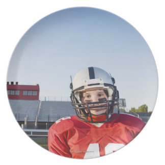 Football player posing on field party plates