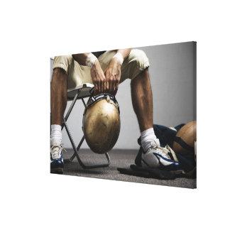 Football player sitting in locker room canvas print