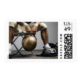 Football player sitting in locker room postage stamp