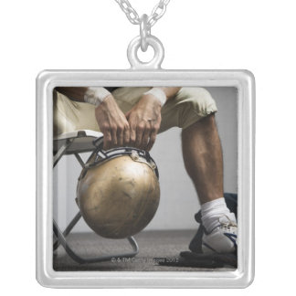 Football player sitting in locker room silver plated necklace