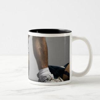 Football player sitting in locker room Two-Tone coffee mug