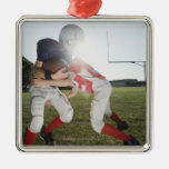 Football player tackling opponent metal ornament