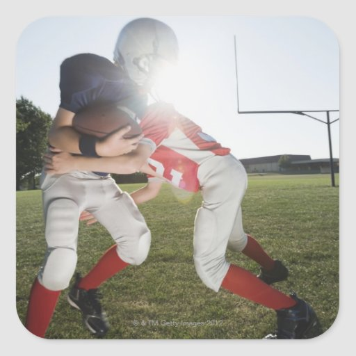 Football player tackling opponent square sticker