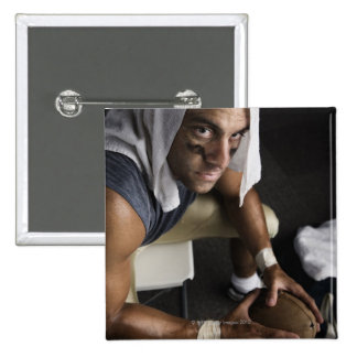 Football player with towel on head holding 2 inch square button