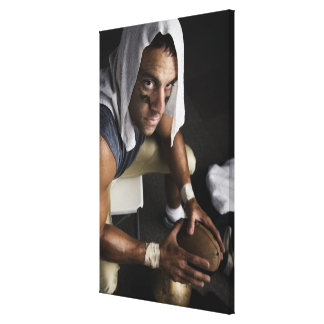 Football player with towel on head holding canvas print