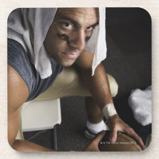 Football player with towel on head holding coaster