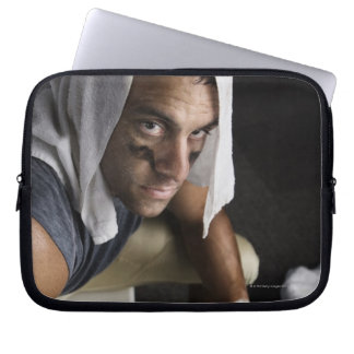 Football player with towel on head holding computer sleeve
