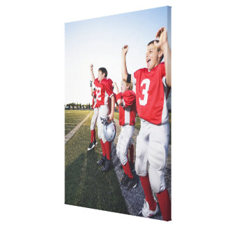 Football players cheering on sideline canvas print
