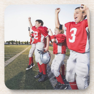 Football players cheering on sideline drink coaster