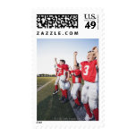 Football players cheering on sideline postage stamp