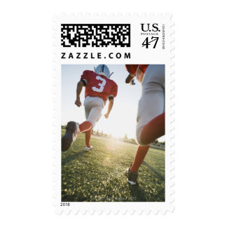 Football players running on field postage
