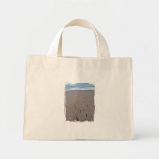 Footprints in beach sand blue ocean in back canvas bags