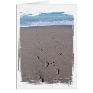 Footprints in beach sand blue ocean in back card