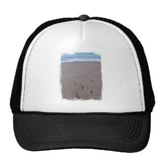 Footprints in beach sand blue ocean in back hats