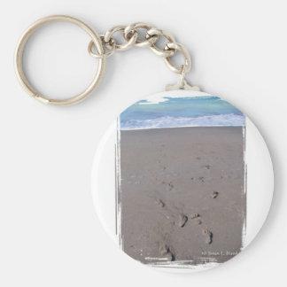 Footprints in beach sand blue ocean in back keychain