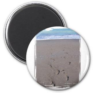 Footprints in beach sand blue ocean in back magnet