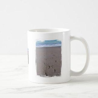 Footprints in beach sand blue ocean in back coffee mugs