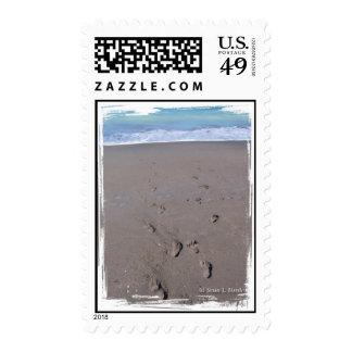 Footprints in beach sand blue ocean in back postage