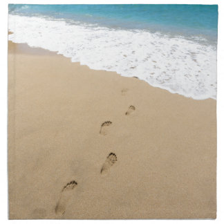 Footsteps in sandy beach leading to blue sea cloth napkin