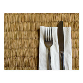Fork and knife on a dried grass mat postcard