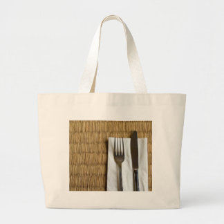Fork and knife on a dried grass mat tote bags