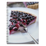 Fork slicing blueberry pie on plate notebook