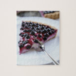 Fork slicing blueberry pie on plate puzzles