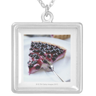 Fork slicing blueberry pie on plate silver plated necklace