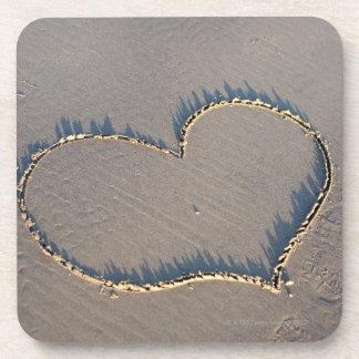 Forma del corazón dibujada en la arena posavaso
