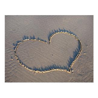 Forma del corazón dibujada en la arena postal