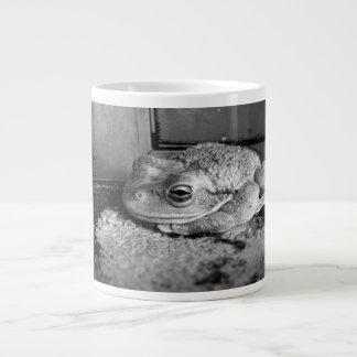 Foto blanco y negro de una rana en un travesaño co taza de café gigante