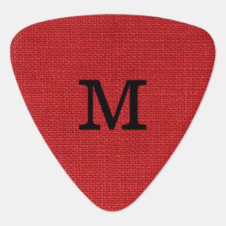 Foto de lino roja de la textura con el monograma púa de guitarra