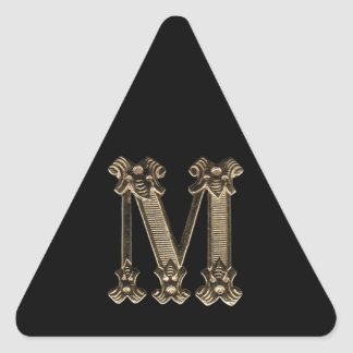 Foto de oro de la letra M en fondo negro Pegatina Triangular