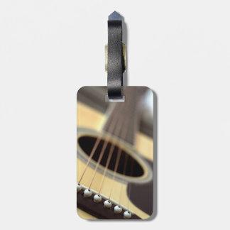 Foto del primer de la guitarra acústica etiqueta de maleta