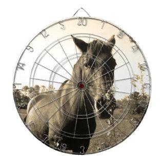 Foto del tono de la sepia del caballo marrón con l tablero de dardos